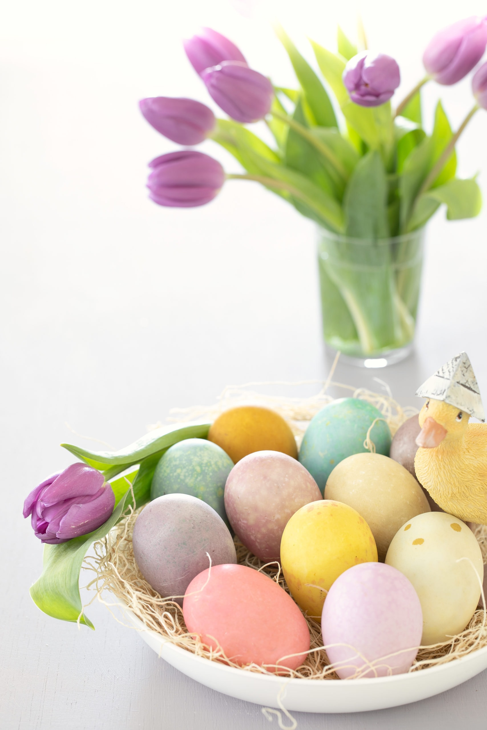 Purple tulips with basket of dyed eggs